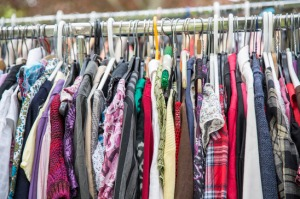 clothes on a rack in a flea market .